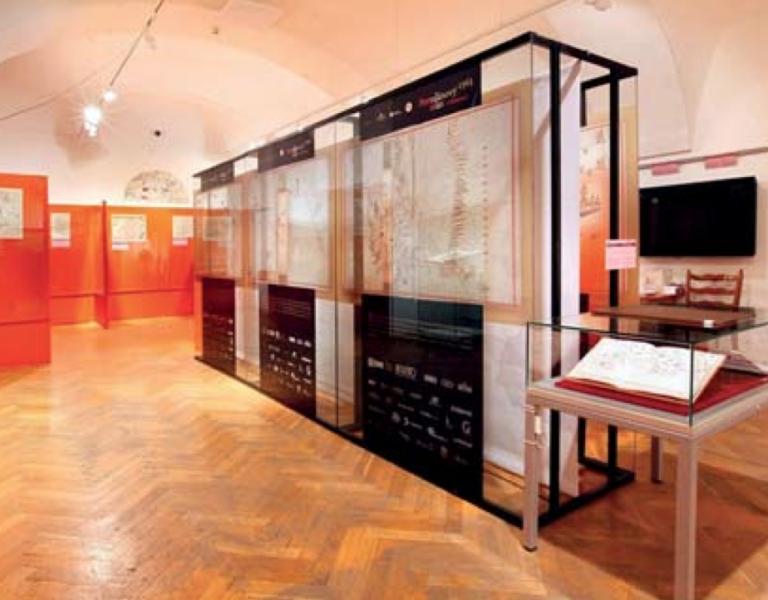 Ukázka části expozice výstavy s atlasy a mapami. Olomouc.